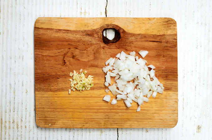 Chopped Onion and Garlic on Wooden Cutting Board