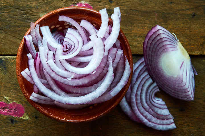 Sliced Red Onions in Rustic Bowl
