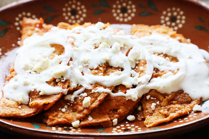 Closeup of Enchiladas Potosinas Topped with Onion and Cream