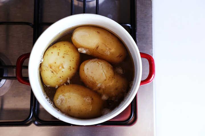 Boiled waxy potatoes in pot.