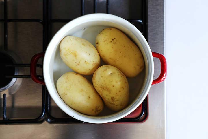 Boiling waxy potatoes in red pot.