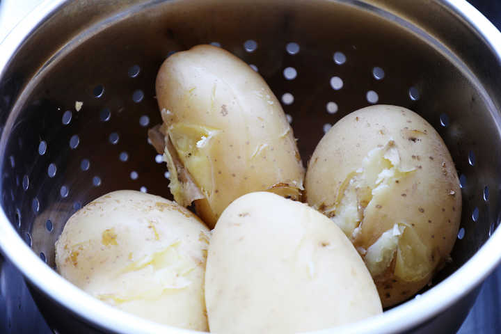 Cooked waxy potatoes in colander.