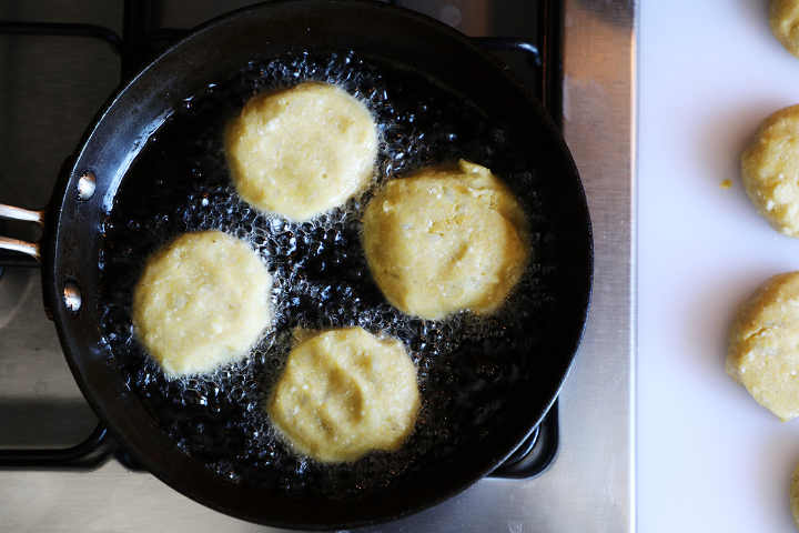 Four potato croquettes frying in pan.