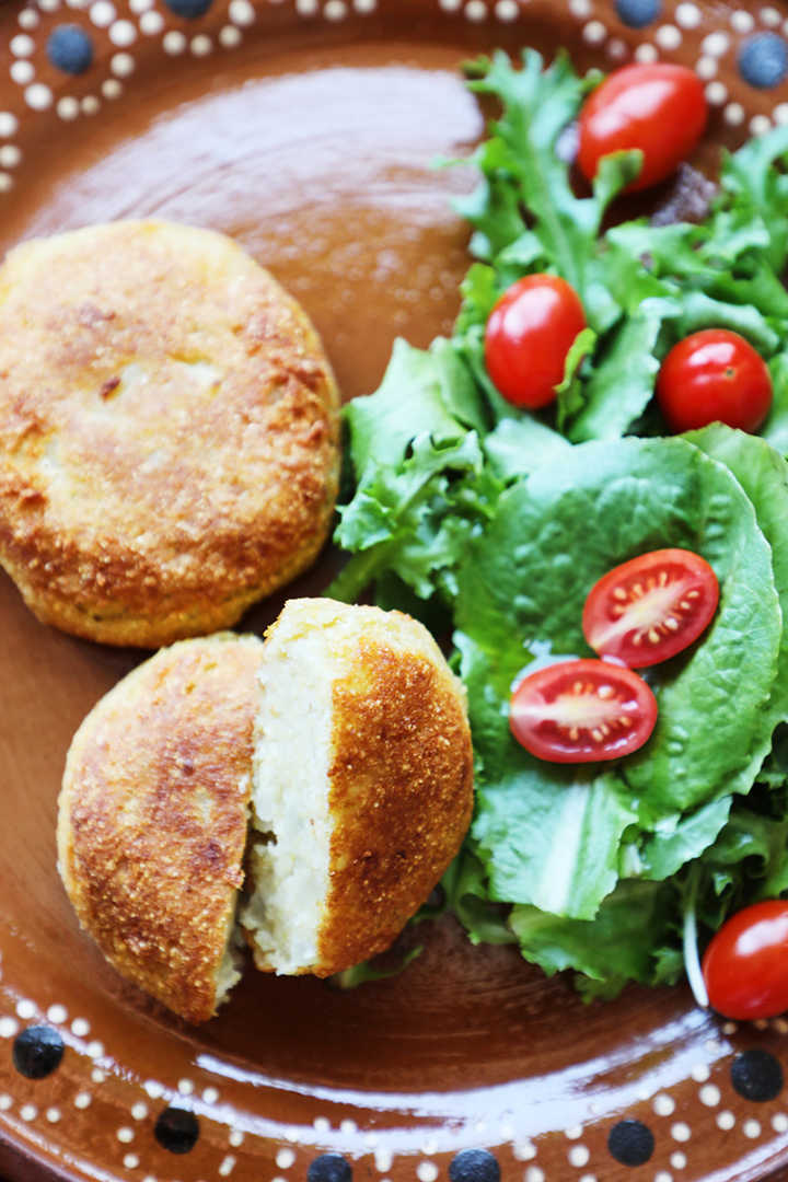 Mashed potato patties and a green salad with tomatoes.