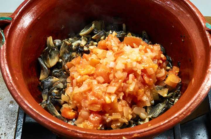 Tomatoes, onions, huitlacoche in clay pot on stove.