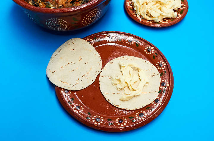 Tortilla and cheese on plate to make quesadillas.