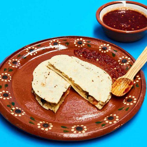 Quesadillas de Huitlacoche served on rustic clay plate.