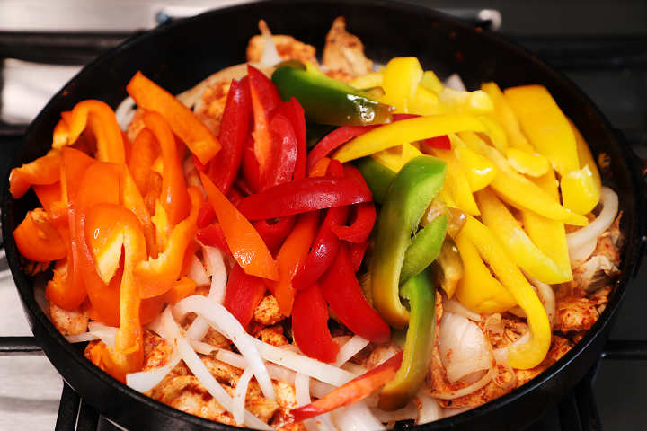 Chicken fajitas in skillet with sliced onions and bell peppers.