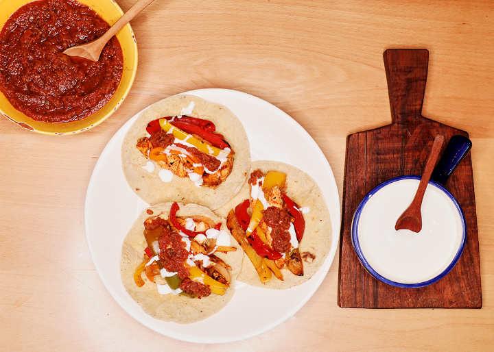 Chicken fajitas taco plate served with cream and salsa roja.