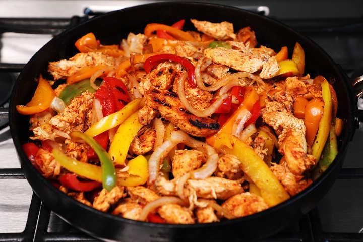 Cooked chicken fajitas in skillet.