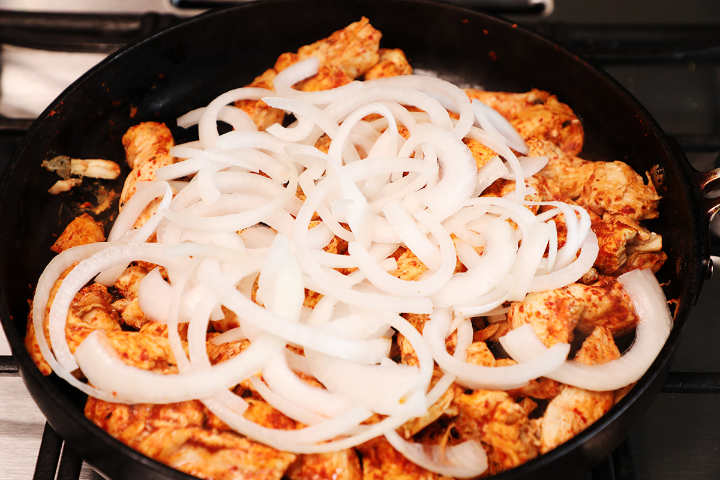 Chicken fajitas in skillet with sliced onions.