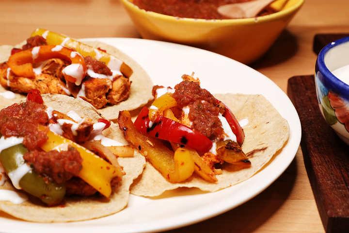 Three chicken fajitas tacos with salsa roja.