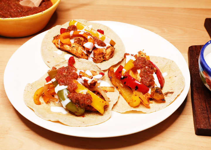 Chicken fajitas tacos with salsa roja on white plate.