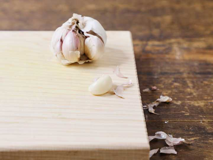 Peeled garlic clove on cutting board.