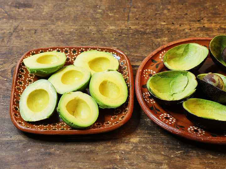 Pitted avocados on plate.