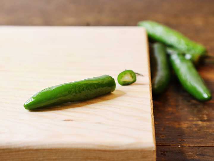 Serrano pepper with stem removed on cutting board.