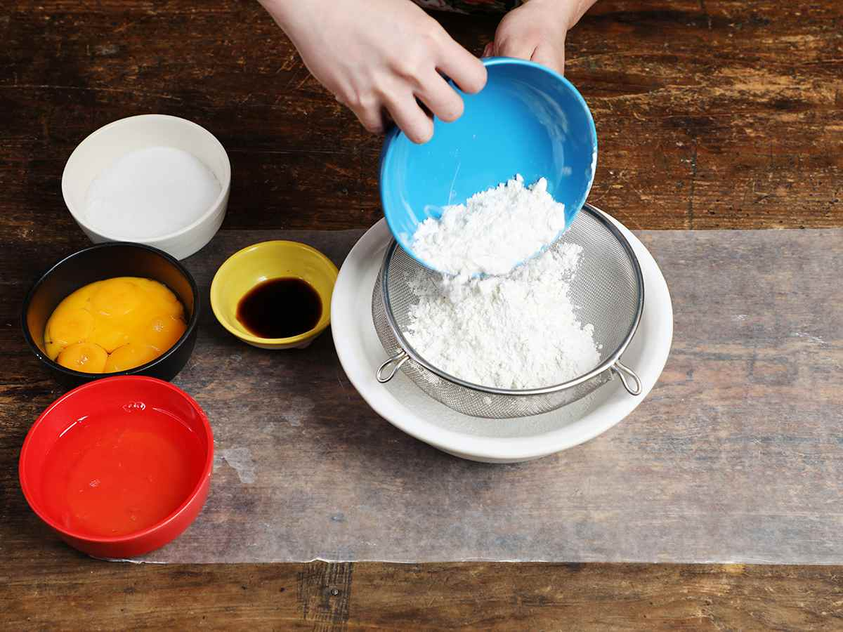 Pouring flour from blue bowl into mesh strainer