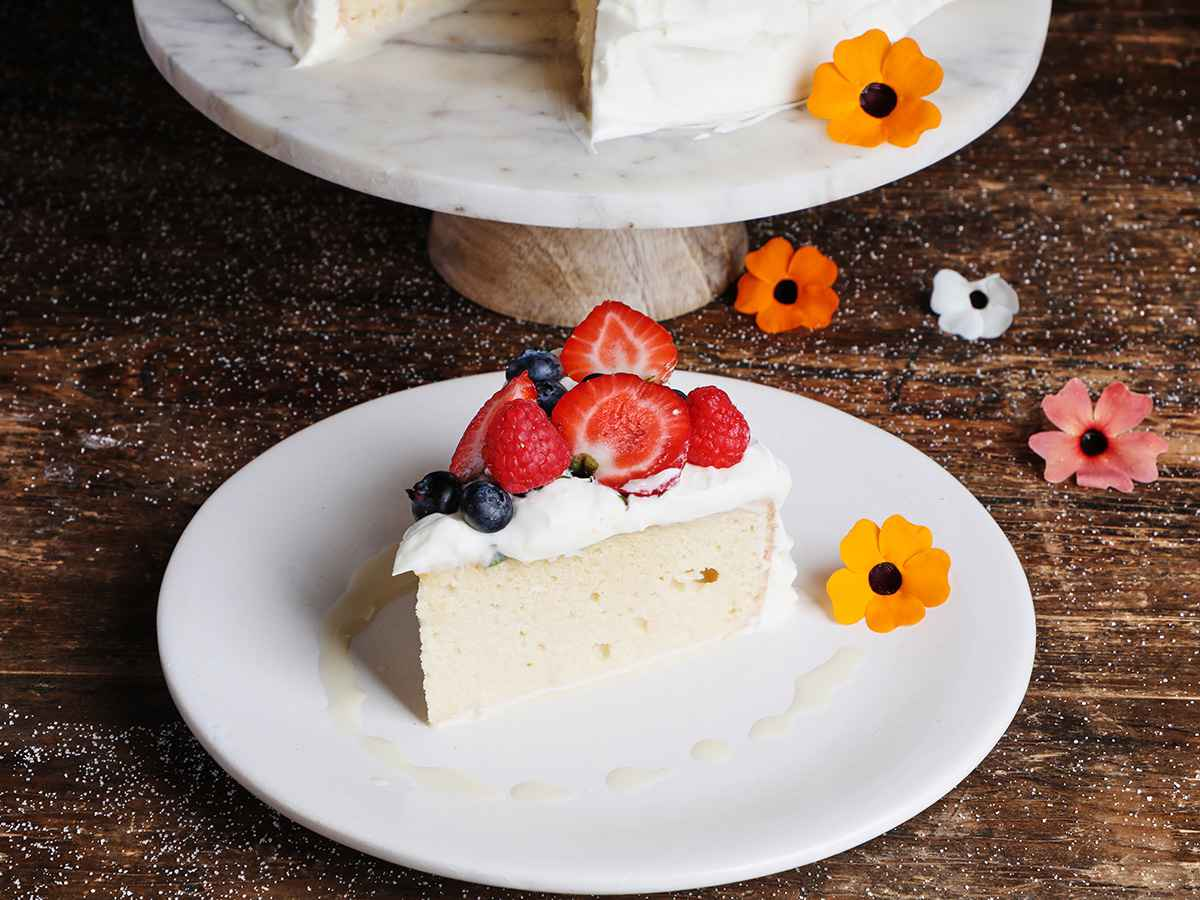 Tres Leches Cake with berries slice on white plate