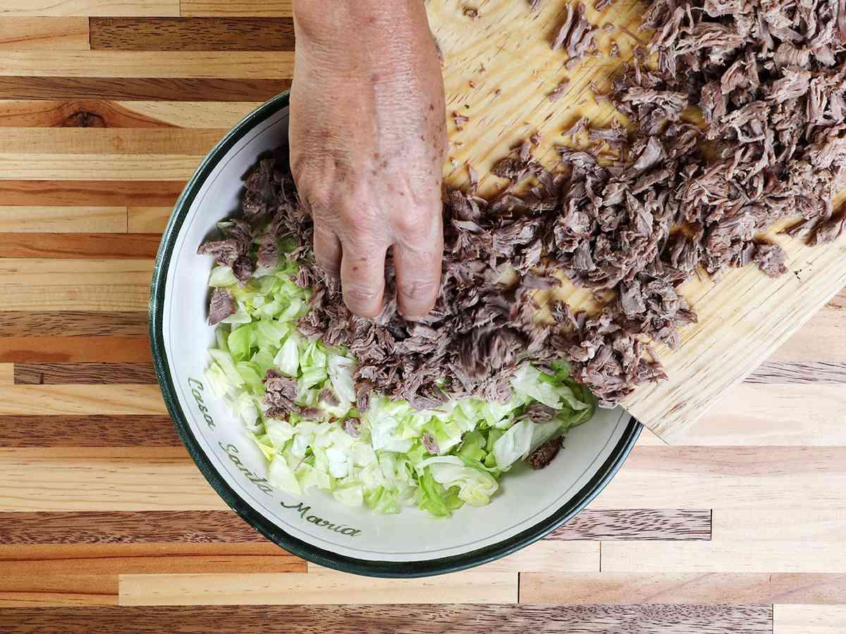 Adding Shredded Beef to Lettuce