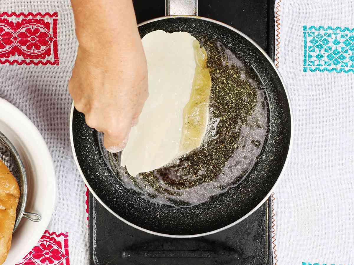 Placing Buñuelo in Frying Pan