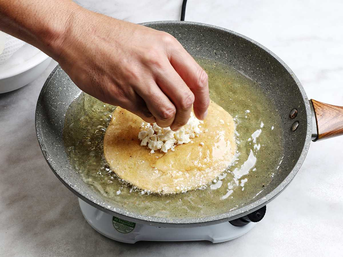 Sprinkling Cheese on Fried Tortilla
